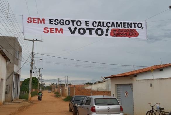 """Após retirada de faixa de protesto do bairro Beira Rio, moradores colocam outra no lugar e reafirmam: """"sem esgoto e calçamento, sem voto"""""""